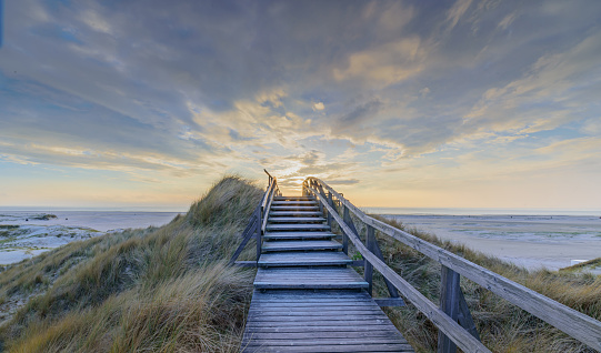 Boardwalk and stairs leading through the dunes to the beach of North Sea by sunset in Norddorf, Amrum, Schleswig-Holstein. Bathing and beach vacation on the North Sea.