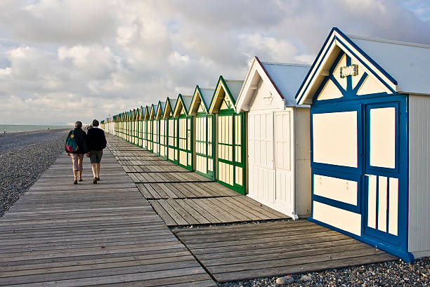 boardwalk beach huts couple walking on boardwalk beach huts somme stock pictures, royalty-free photos & images