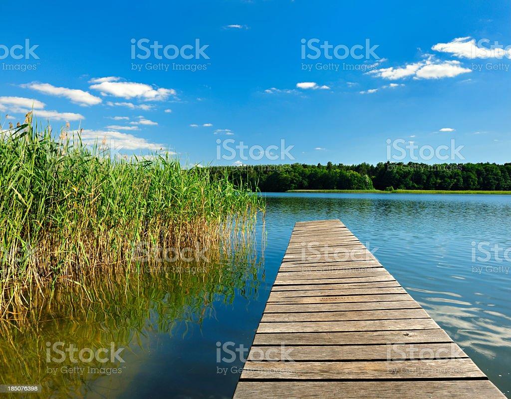 Boardwalk Dock on Lake under Cloudy Summer Sky royalty-free stock photo