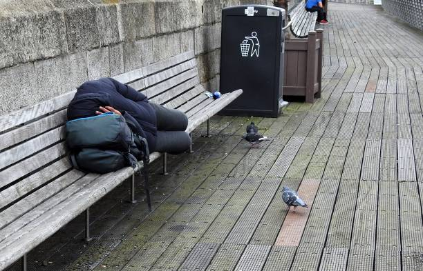 Boardwalk sleeper Anonymous person sleeping on River Liffey boardwalk bench, in Dublin city centre, Ireland. homelessness stock pictures, royalty-free photos & images