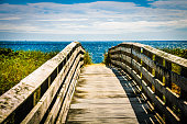 A wooden boardwalk leads across a low sand dune toward the beach and blue ocean beyond.