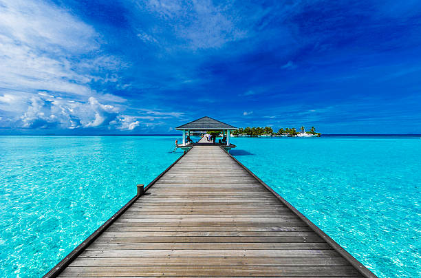 Boardwalk to paradise A boardwalk leads to an island in the Maldives beach hut stock pictures, royalty-free photos & images