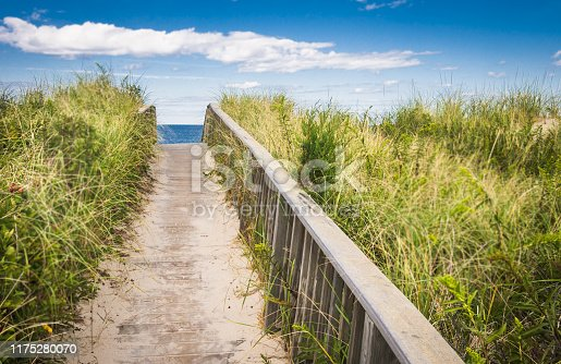 A narrow wooden boardwalk with a railing leads over a sand dune through the beach grasses to the beach beyond on Cape Cod.