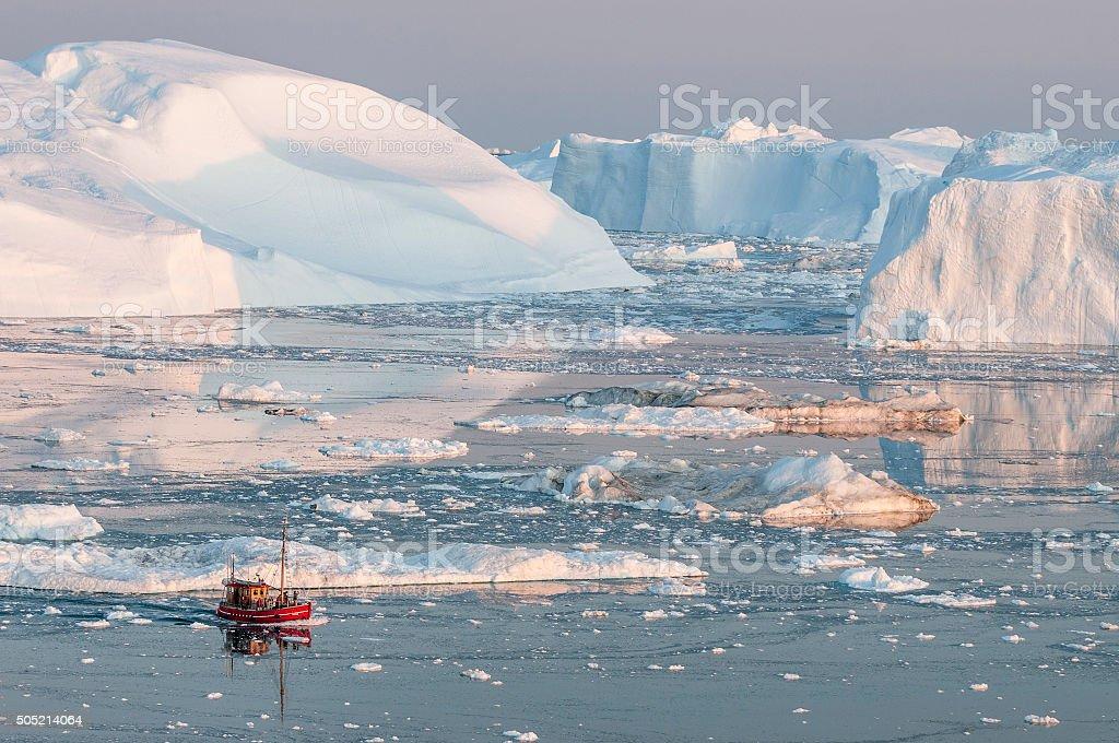 Boat among iceberg in Greenland stock photo