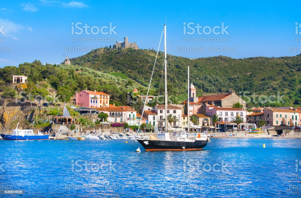 Boat and beach hotels in Collioure village with a windmill at the top of the hill, Roussillon, Vermilion coast, Pyrenees Orientales, France stock photo