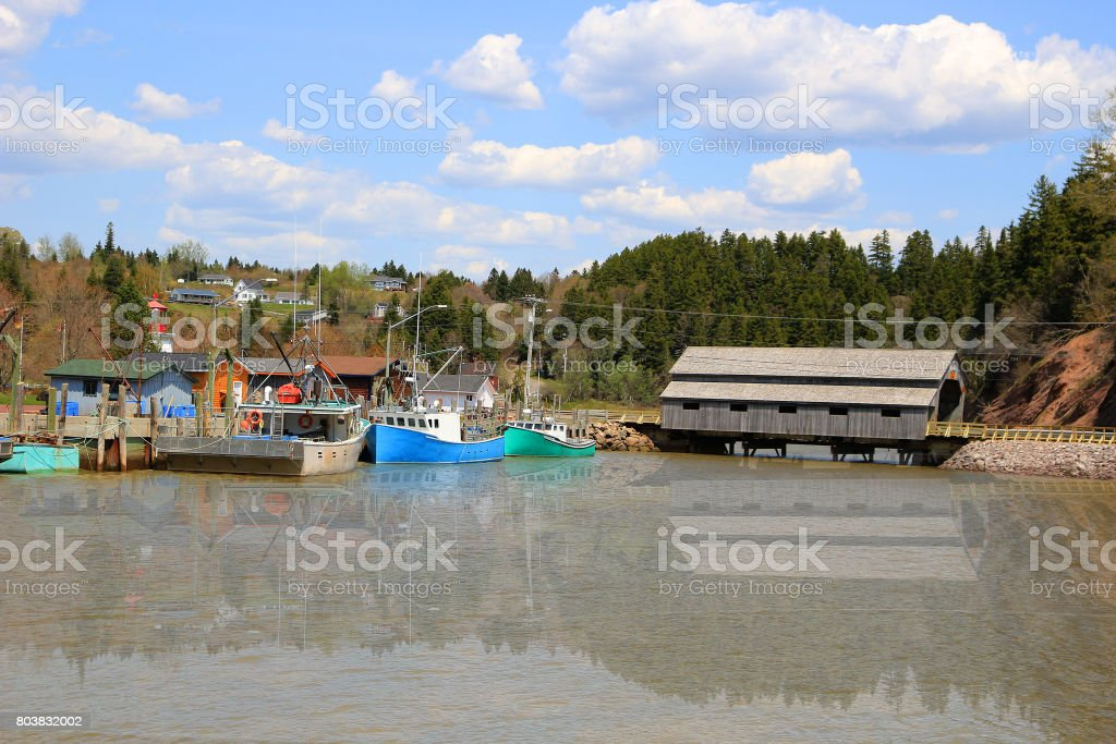 Boat and covered Bridge in St. Martins, New Brunswick during High Tide on the Bay of Fundy, Canada stock photo