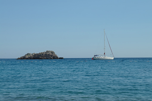 Boat and lonely rock in the sea