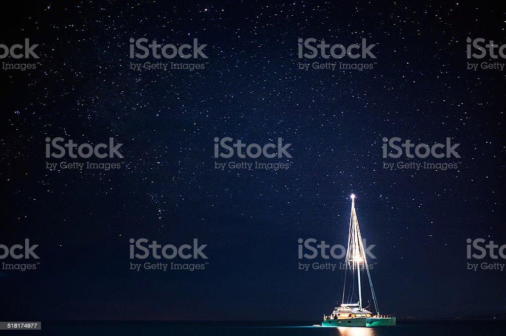 Barco ancorado à noite, sob as estrelas - foto de acervo