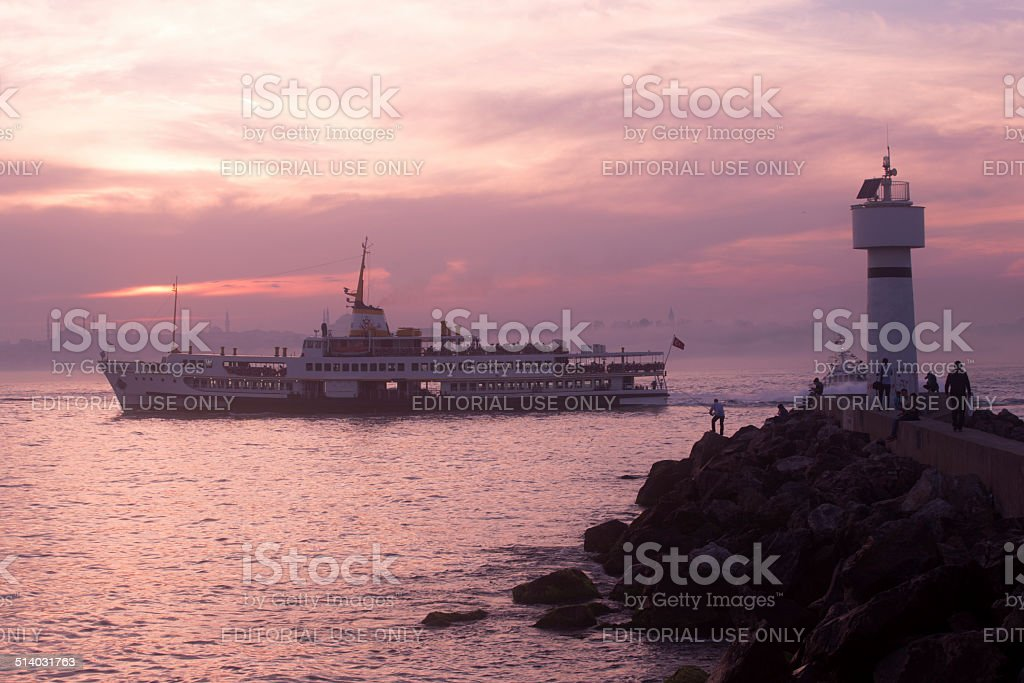 boat at coast of istanbul during foogy sunset in turkey stock photo