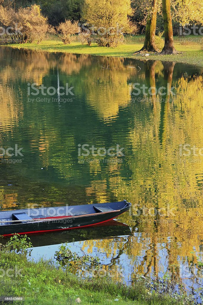 Boat at Crnojevica river with colorful trees reflection, Montene stock photo