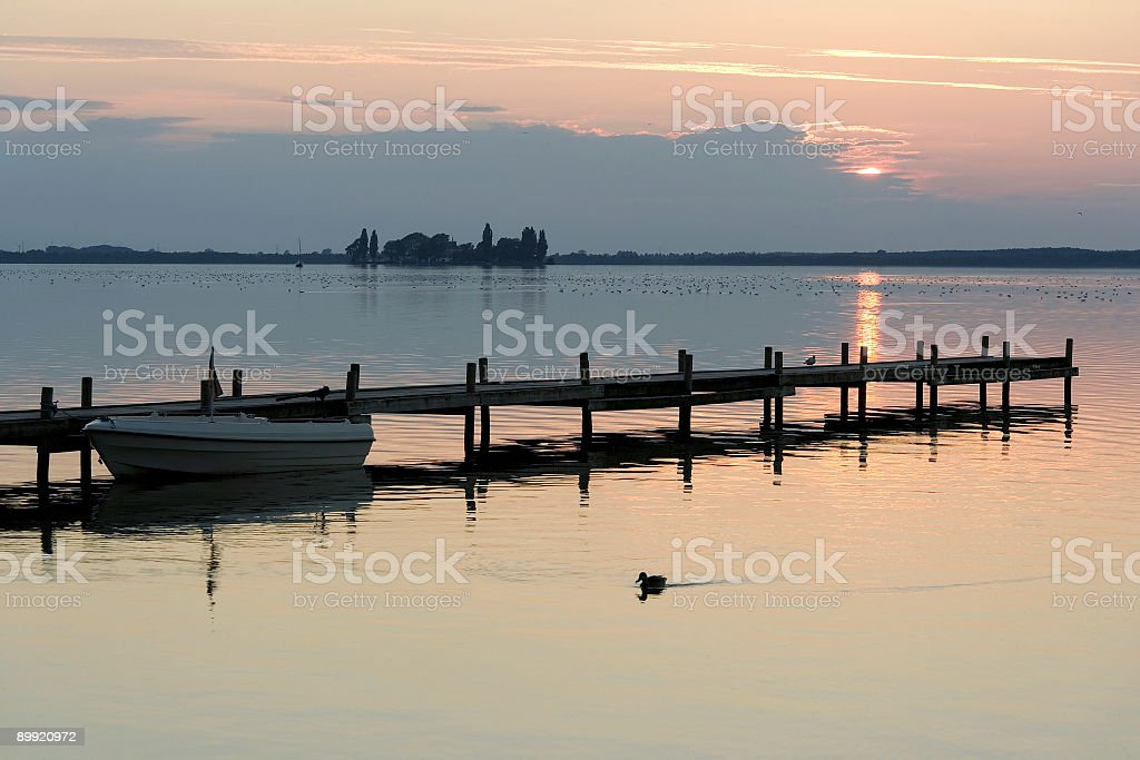Boat at lakeside jetty with sunset cloudscape royalty-free stock photo