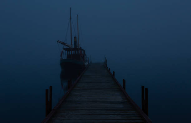Boat at the pier in time of fog by night stock photo