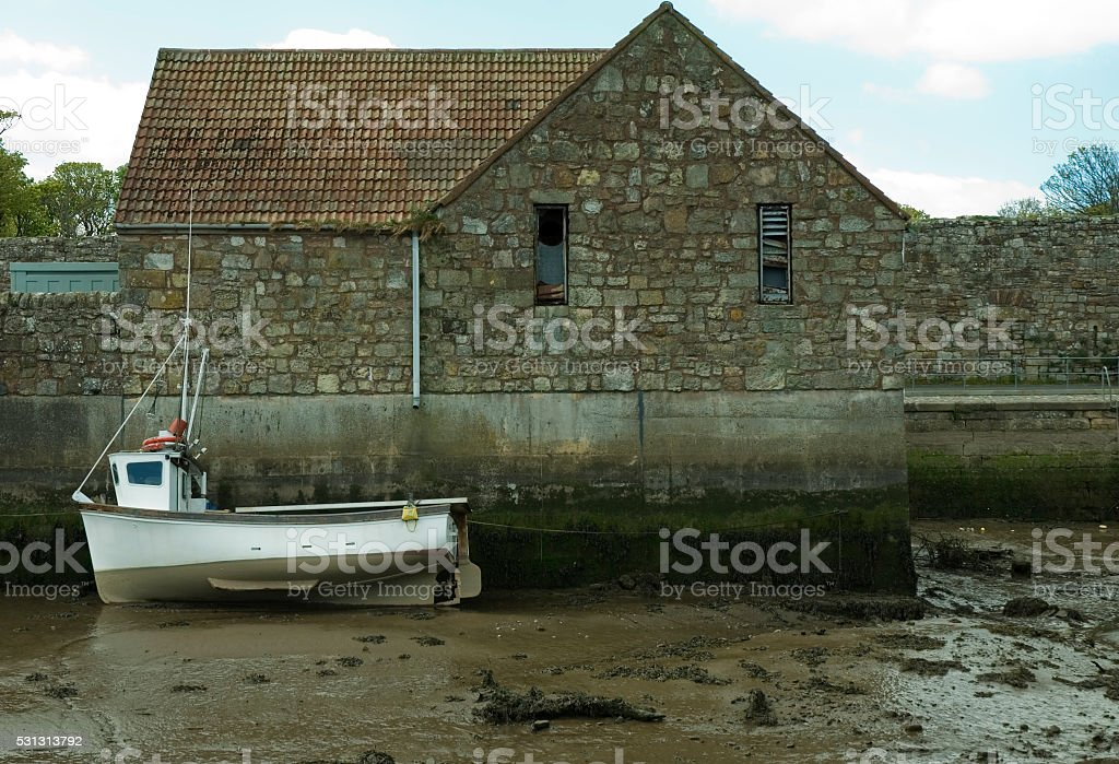 boat beached beside building stock photo