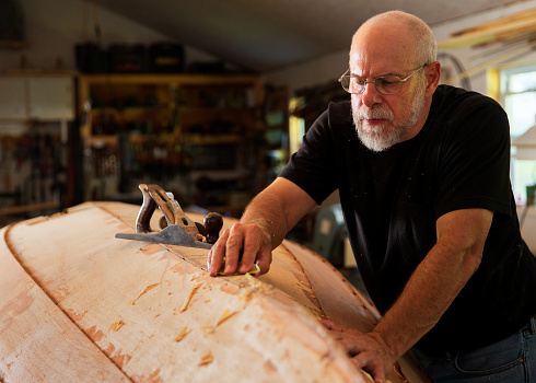 Portrait of a senior man building a boat.