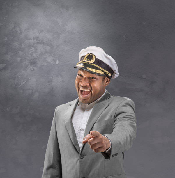 Boat captain afro american in suit pointing and smiling at you Boat captain in suit pointing and smiling at you sailor hat stock pictures, royalty-free photos & images