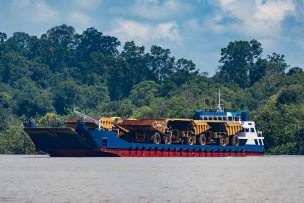 Boat carrying huge trucks for coal transportation in Berau, Kalimantan stock photo