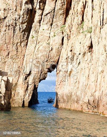 tourist boat driving on the ocean through a crevice