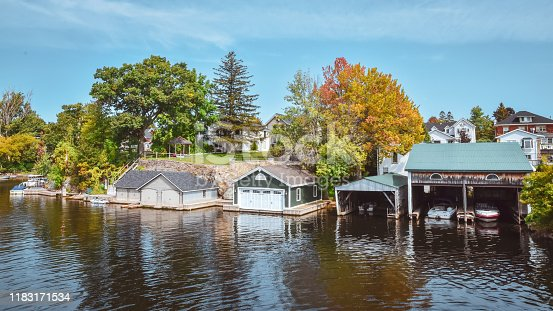 Boat cottage dock. Lake Ontario in autumn. Colorful vivid trees. Canada, United States of America.