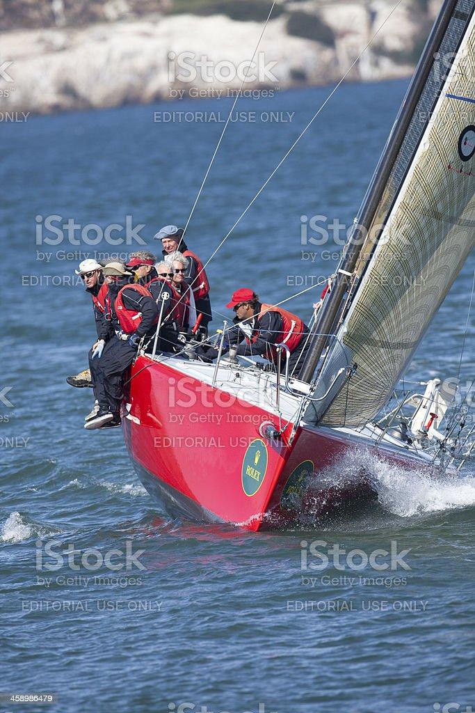Boat Crew Balancing Their Sailboat While Tacking stock photo