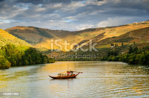 A traditional Portuguese rabelo boat cruising down the Duoro River, Portugal.  Terraced vineyards cover the hills next to the river.