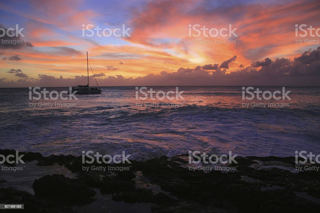 Boat cruising in front of a breathtaking sunset stock photo