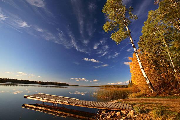 Boat dock and autumn trees along a Saskatchewan Lake stock photo