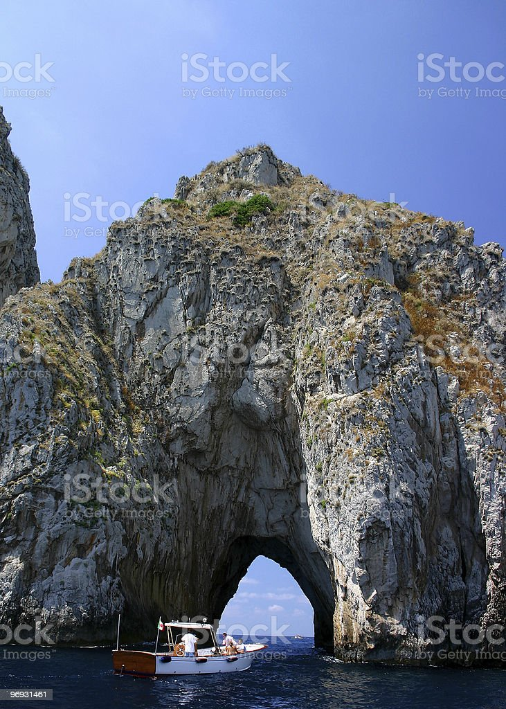 Boat entering rock tunnel royalty-free stock photo