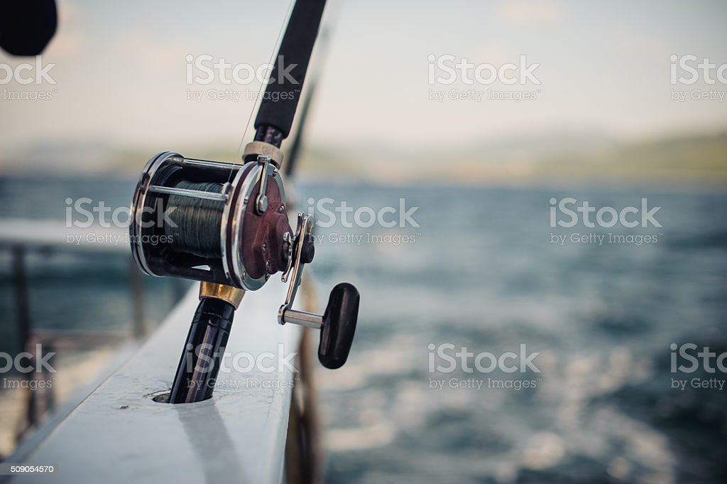 Boat fishing rods over a beautiful cloudy seascape stock photo