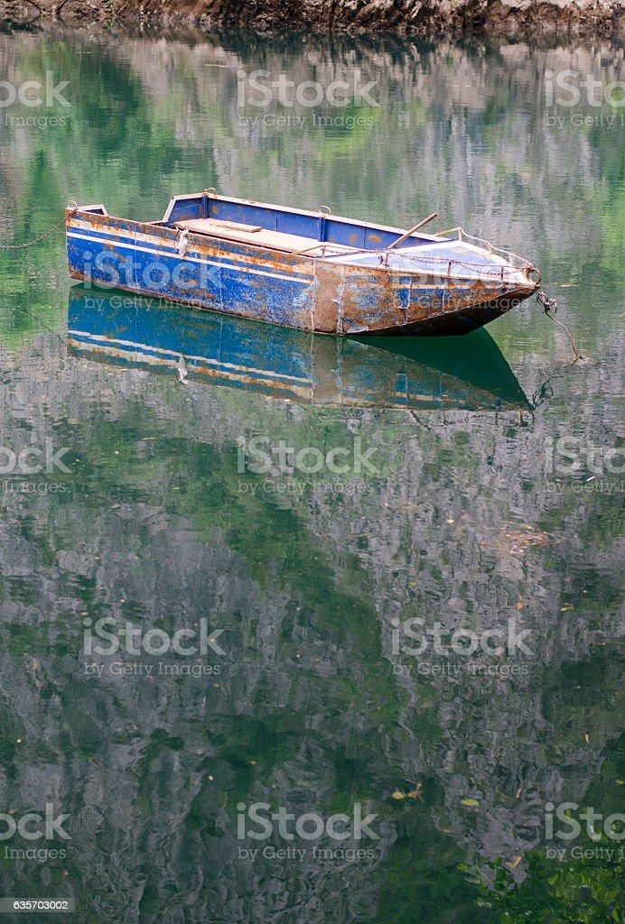 Boat floating on calm lake water royalty-free stock photo