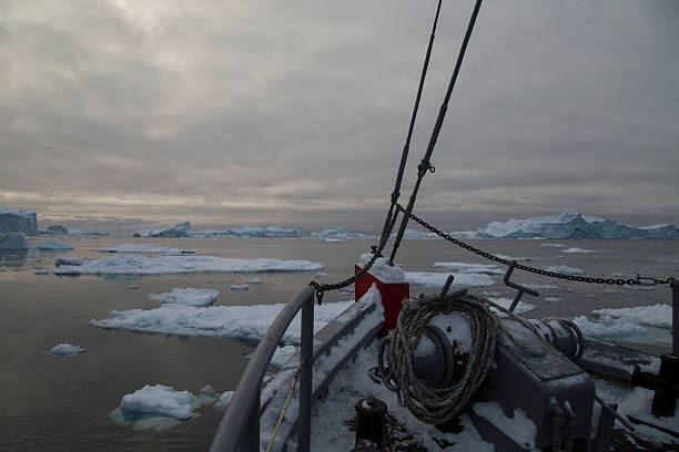 Boat floating through icy polar water between floe stock photo