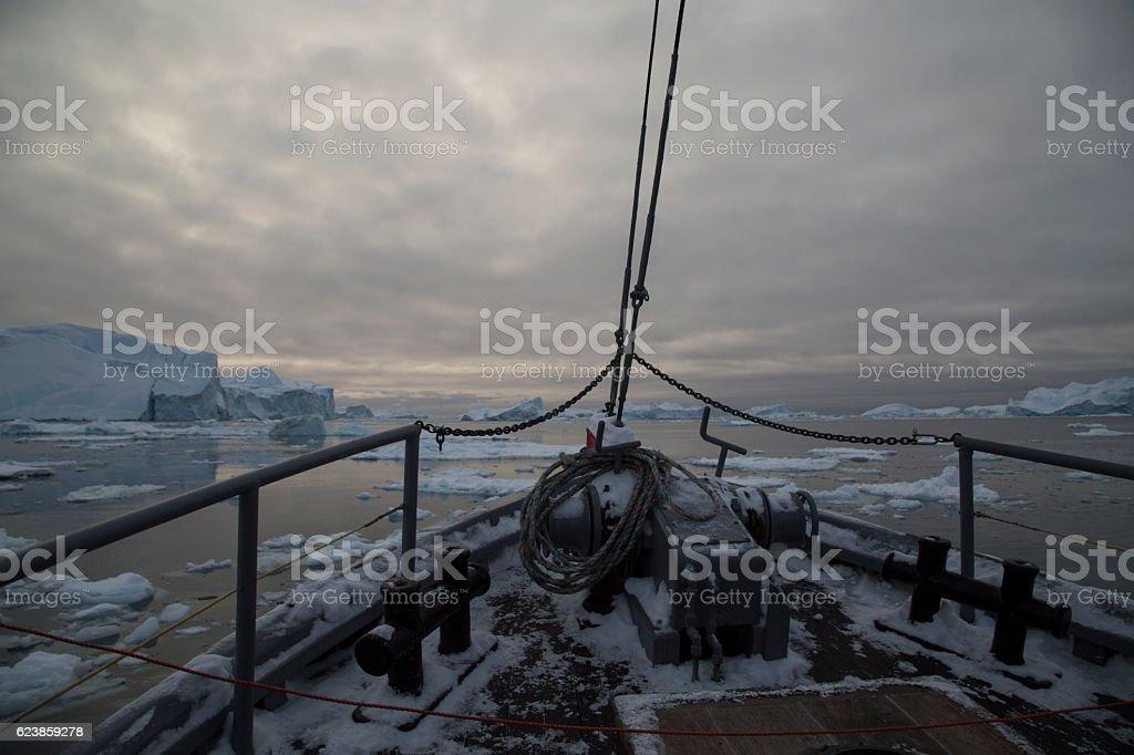 Boat floating through icy polar water near iceberg stock photo