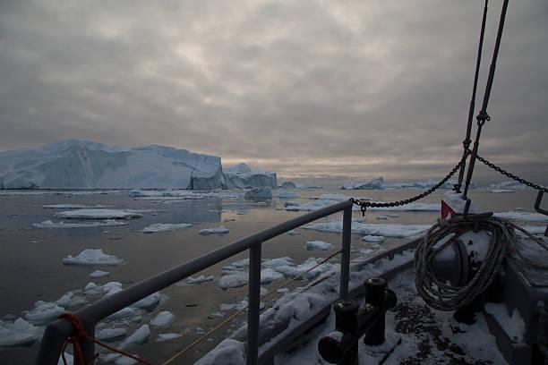 Boat floating through icy polar water near icebergs stock photo