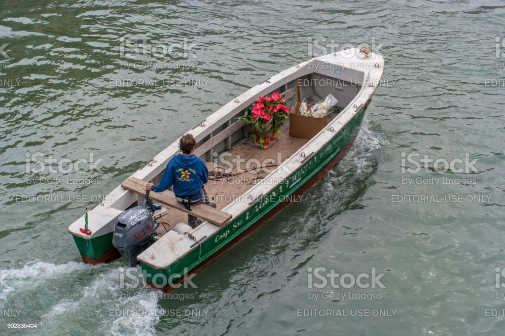 Venice, Italy - October 13, 2017: Boat for delivery of flowers swims to fulfill the order. The boat is run by an employee in branded clothes. View from above. stock photo
