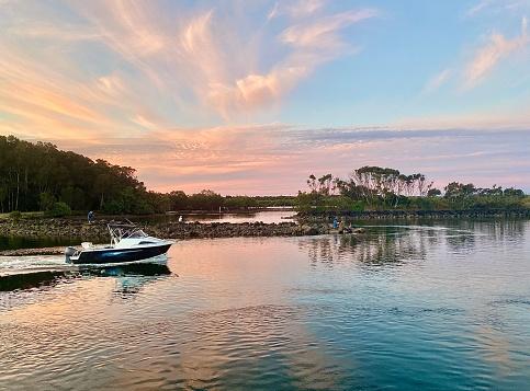 Horizontal seascape of river boat moving along still water coastline under a soft pastel color sky at Brunswick Heads near Byron Bay NSW Australia