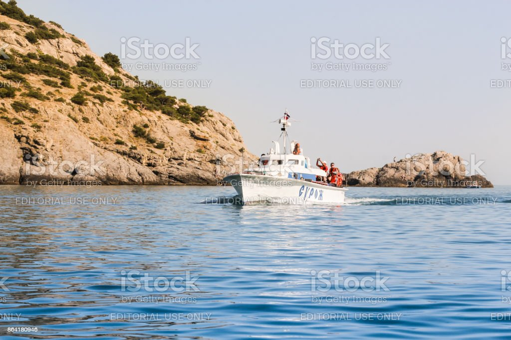 Boat going along the rocks. royalty-free stock photo