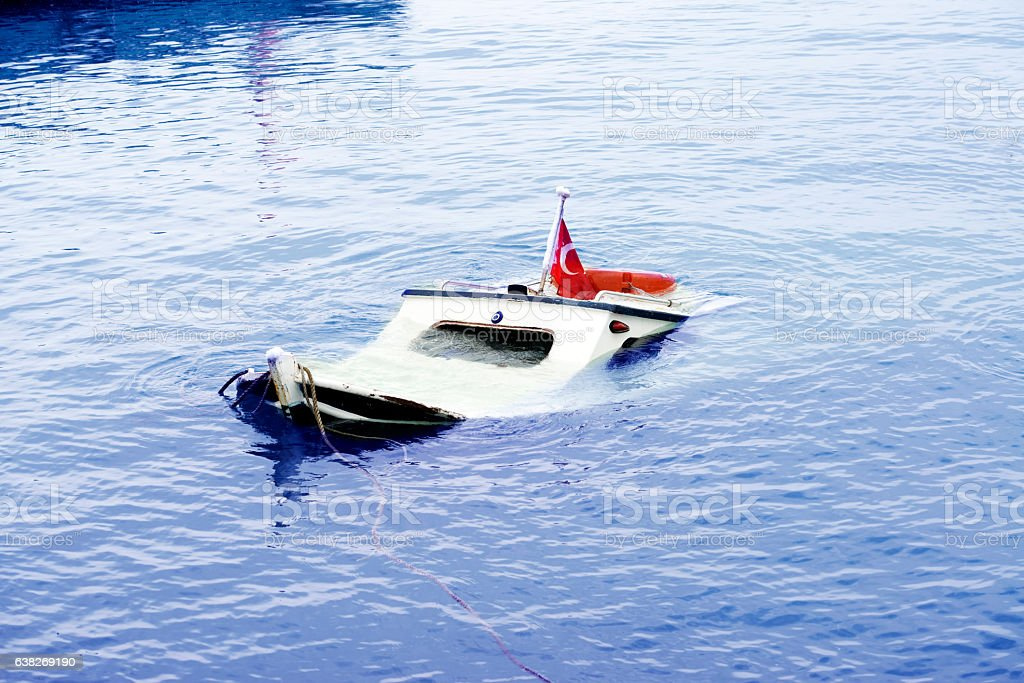 Boat going down in sea stock photo