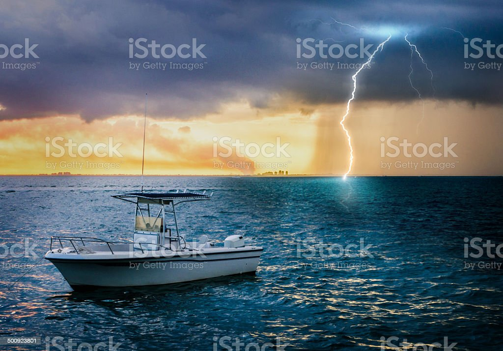 Boat in a storm with lightning background stock photo