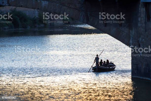 Photo of Boat in a waters of Arno river during sunset, Florence, Tuscany, Italy