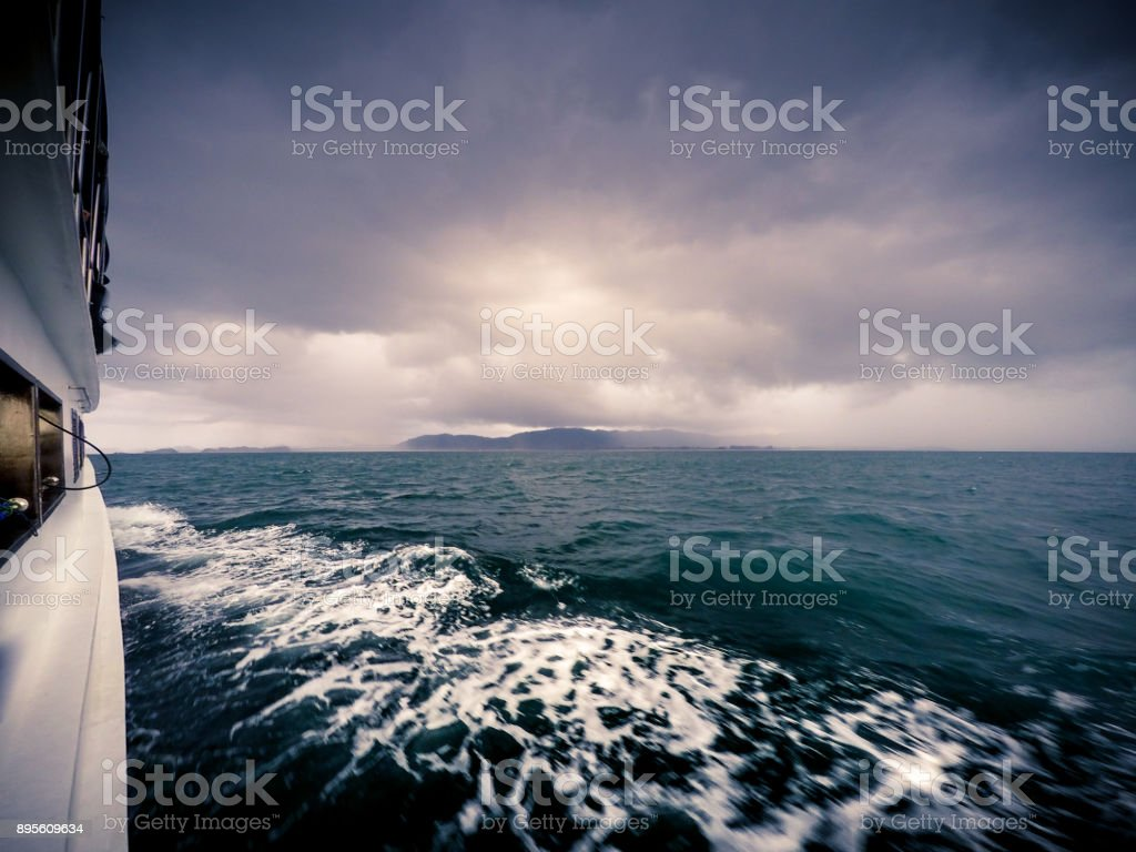 A boat travels below the dark clouds of a tropical Tornado moving...