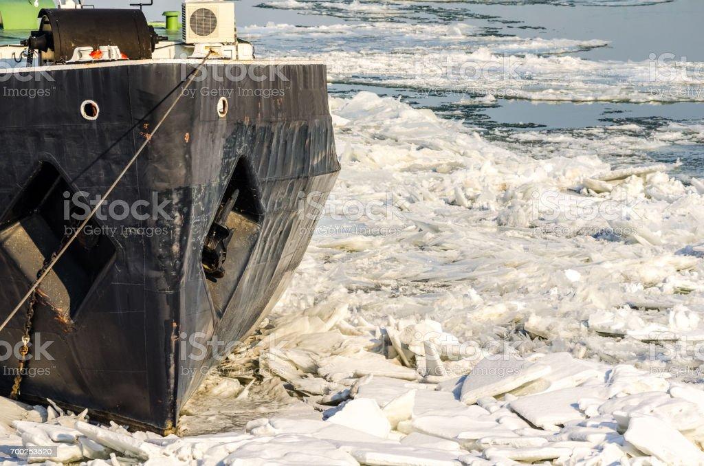 Boat in ice. Boat stuck in ice of frozen river. Danube river, Novi Sad, Serbia. Winter image. stock photo