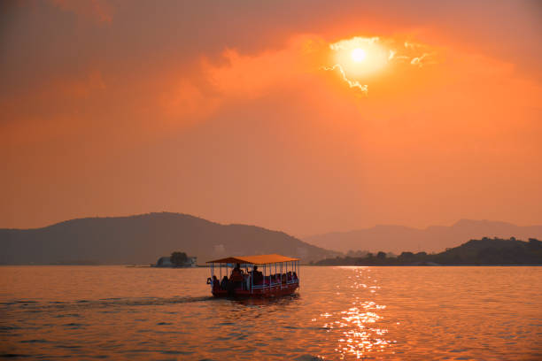 Boat in lake Pichola on sunset. Udaipur, Rajasthan, India Tourist boat in lake Pichola on sunset. Udaipur, Rajasthan, India lake pichola stock pictures, royalty-free photos & images