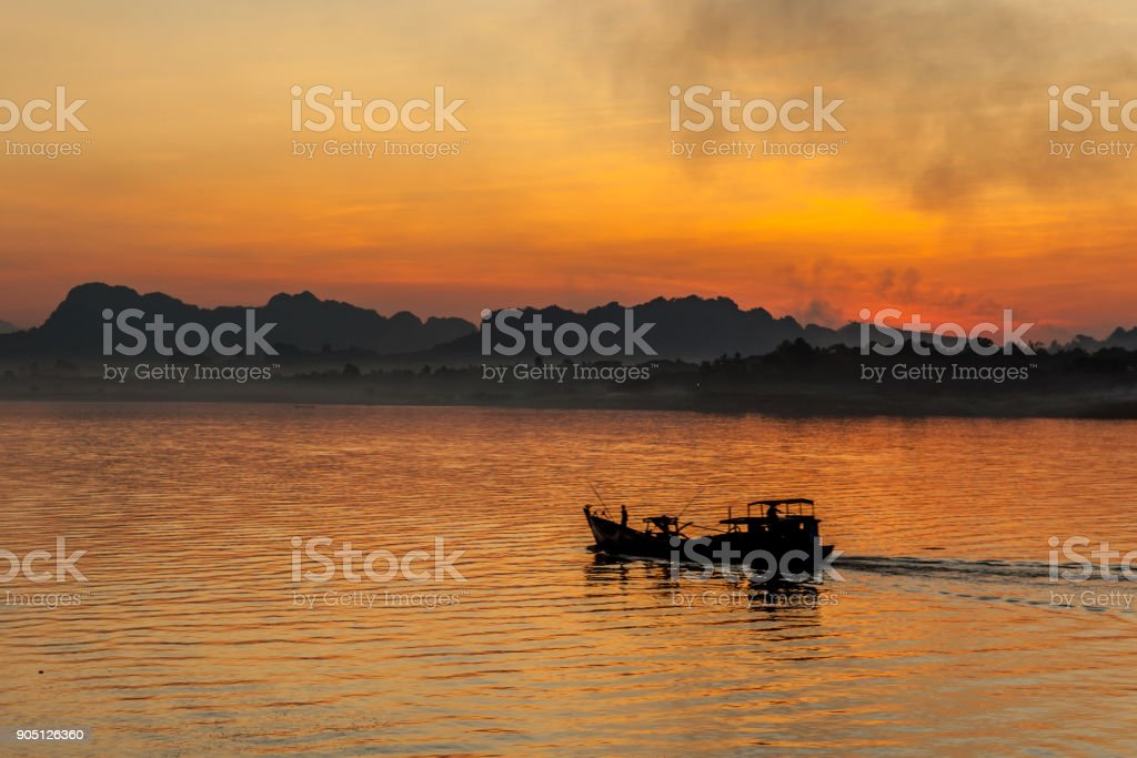 Boat in Salween River at sunset in Hpa-An province, Myanmar. stock photo