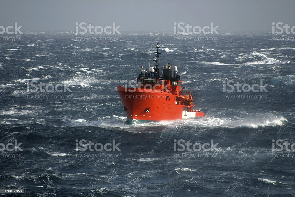 boat in storm at sea stock photo