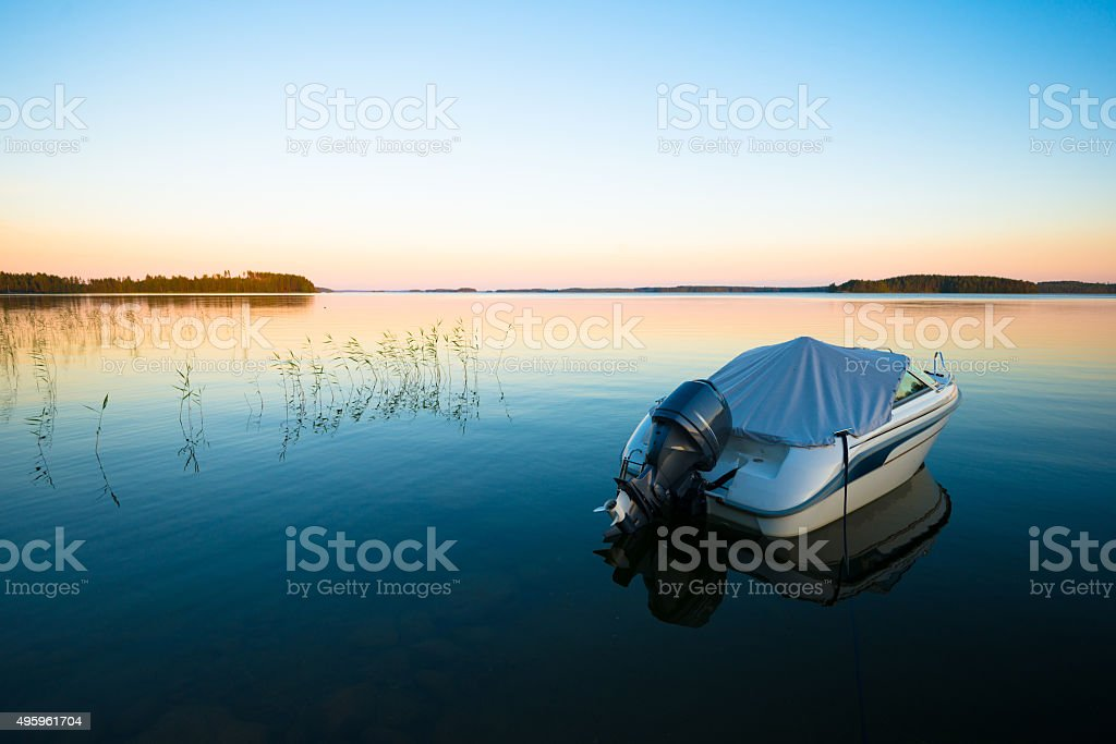 Boat in Sunset on Calm Lake stock photo