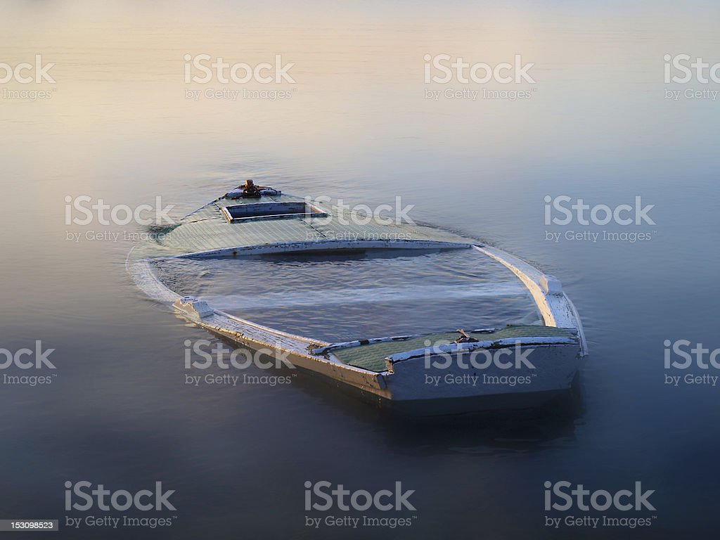 Boat in the fog taking on water and sinking stock photo