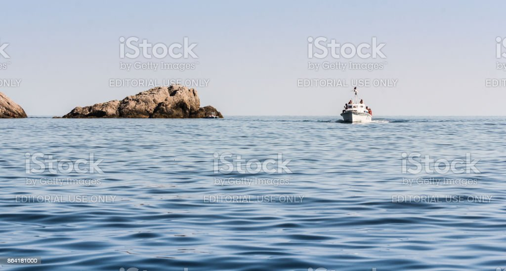 A boat in the sea by the stone. royalty-free stock photo