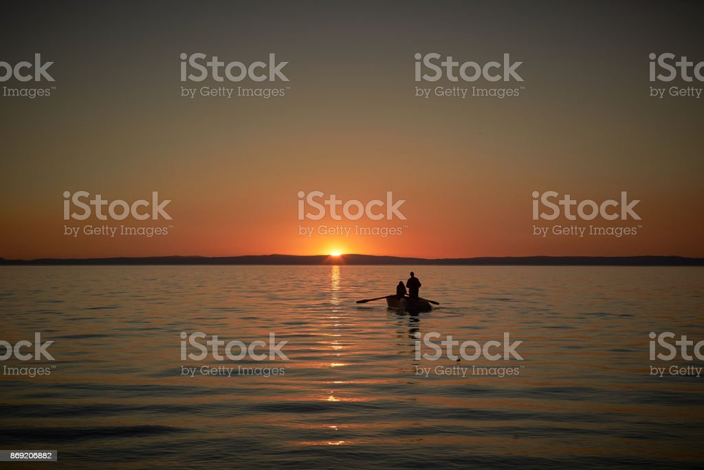 Boat in the sea with two fishermen in it, nets in the sea. Sunset or sunrise stock photo