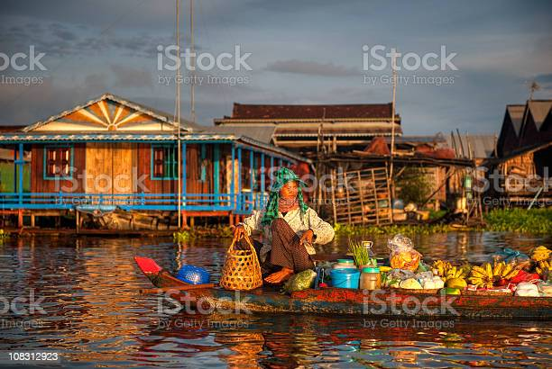 Boat in water in front of colorful Cambodian village