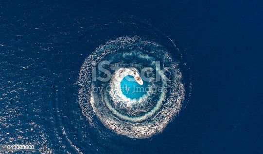 istock A boat is driving in a circle and produces a big whirlpool 1043003600