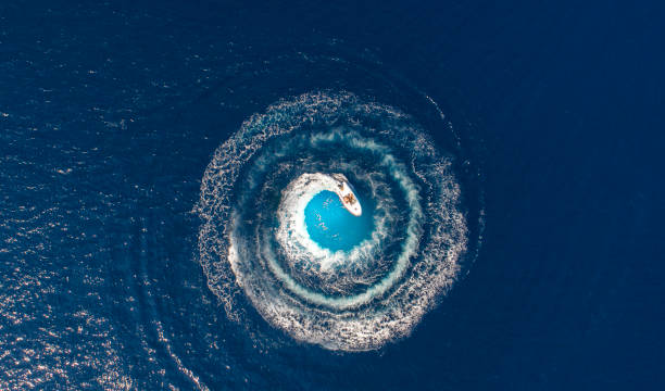 A boat is driving in a circle and produces a big whirlpool stock photo